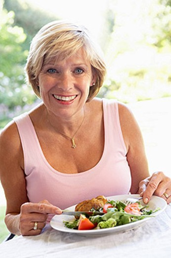 Stock Photo: 1888R-21320 Middle Aged Woman Eating An Al Fresco Lunch