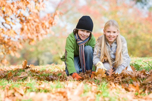 Two young children outdoors at park playing in leaves and smiling selective focus : Stock Photo
