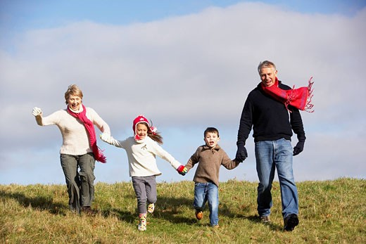Grandparents And Grandchildren Running In The Park : Stock Photo