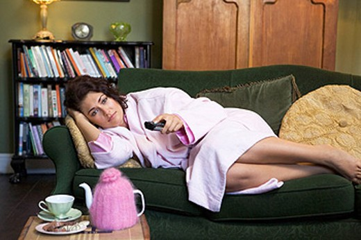 Young woman lying on sofa at home watching television : Stock Photo