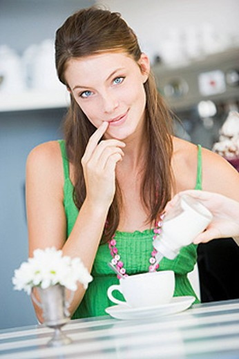Young woman sitting at a table drinking tea : Stock Photo