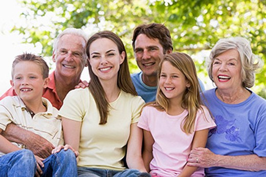 Extended family sitting outdoors smiling : Stock Photo