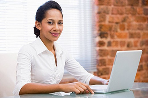 Businesswoman in office with laptop smiling : Stock Photo