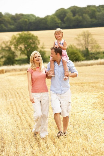 Family Walking Together Through Summer Harvested Field : Stock Photo