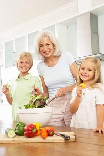 Grandchildren Helping Grandmother To Prepare Salad In Modern Kitchen : Stock Photo