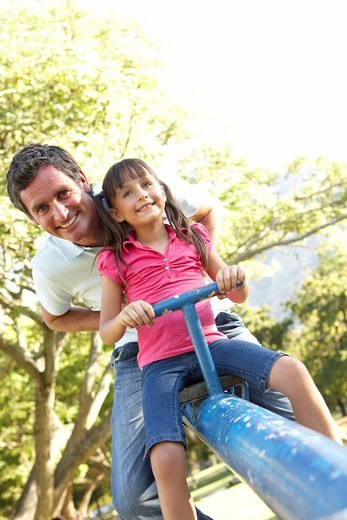 Father And Daughter Riding On See Saw In Playground : Stock Photo