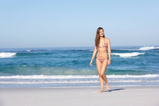 Young Woman Walking Along Sandy Beach On Holiday Wearing Bikini : Stock Photo
