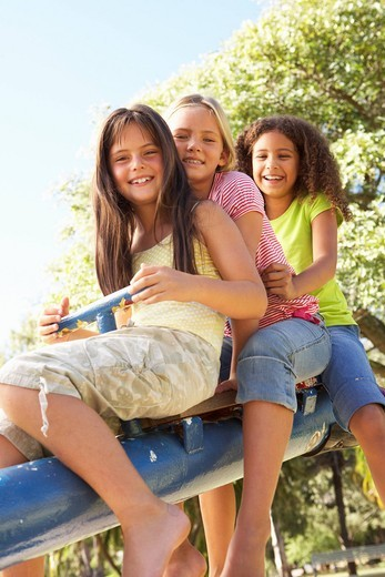 Stock Photo: 1888R-25063 Three Girls Riding On See Saw In Playground