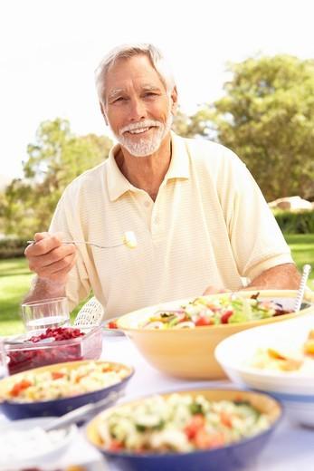 Stock Photo: 1888R-25164 Senior Man Enjoying Meal In Garden