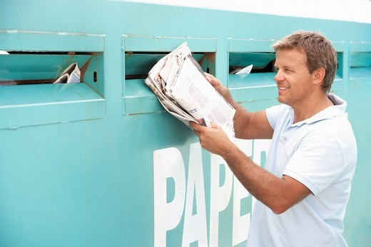 Man At Recycling Centre Disposing Of Old Newspapers : Stock Photo