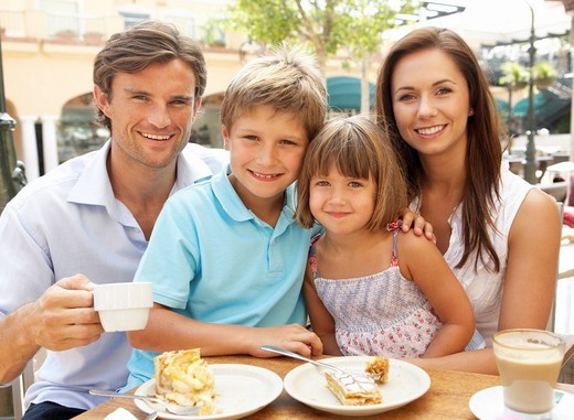 Young Family Enjoying Cup Of Coffee And Cake In Café Together : Stock Photo