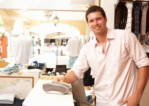 Male Sales Assistant At Checkout Of Clothing Store : Stock Photo