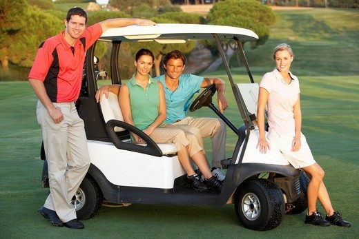 Group Of Friends Riding In Golf Buggy On Golf Course : Stock Photo