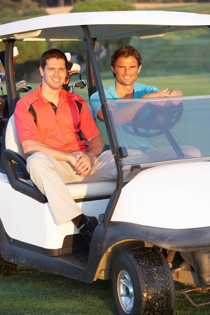 Stock Photo: 1888R-25692 Two Male Golfers Riding In Golf Buggy On Golf Course
