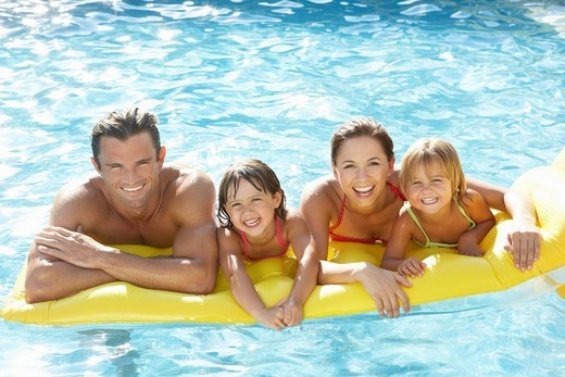 Stock Photo: 1888R-26061 Young family, parents with children, in pool