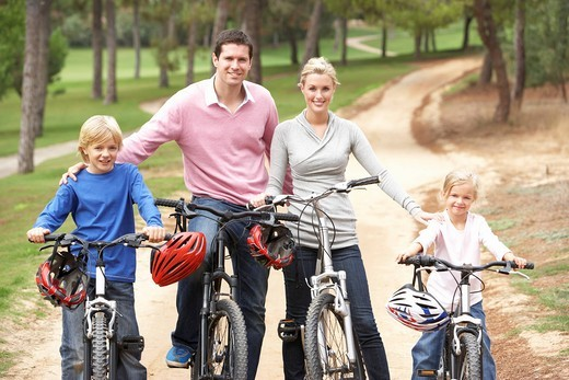 Family enjoying bike ride in park : Stock Photo