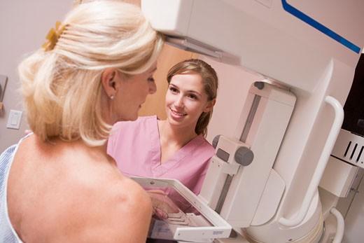 Nurse Assisting Patient Undergoing Mammogram : Stock Photo
