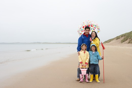 Stock Photo: 1888R-38410 Happy family on beach with umbrella