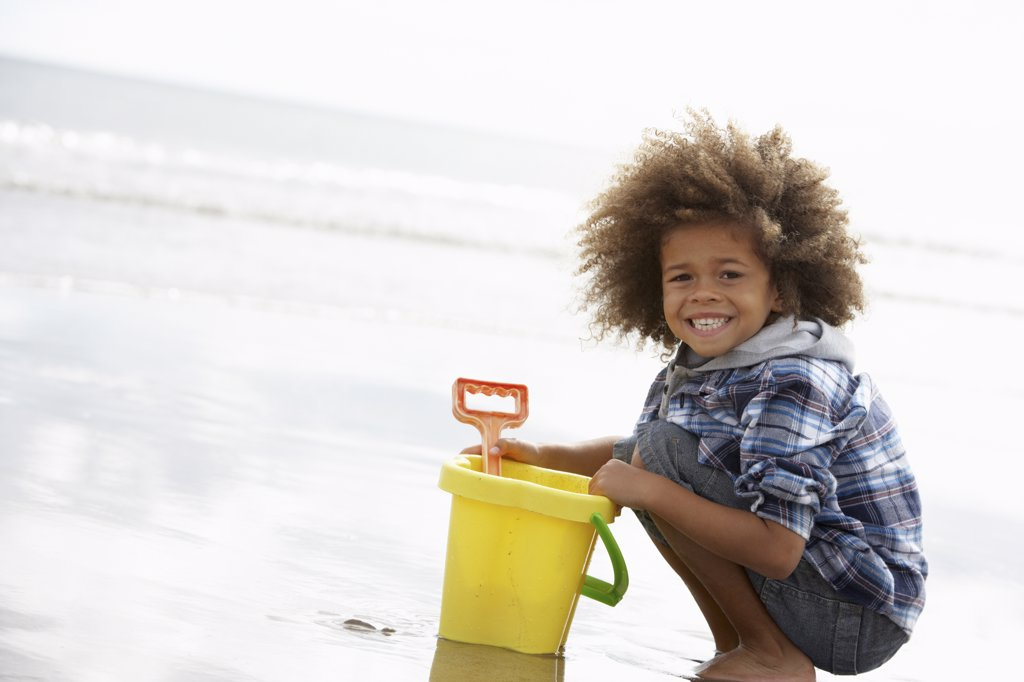 Happy boy at beach with bucket and spade : Stock Photo