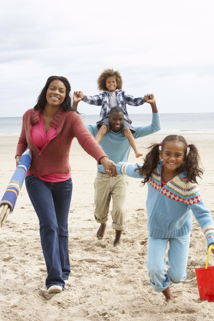 Happy family running on beach : Stock Photo