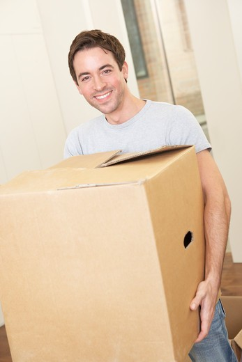 Stock Photo: 1888R-38803 Young man on moving day holding and carrying cardboard box