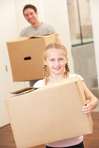 Stock Photo: 1888R-38804 Girl with young man on moving day carrying cardboard box