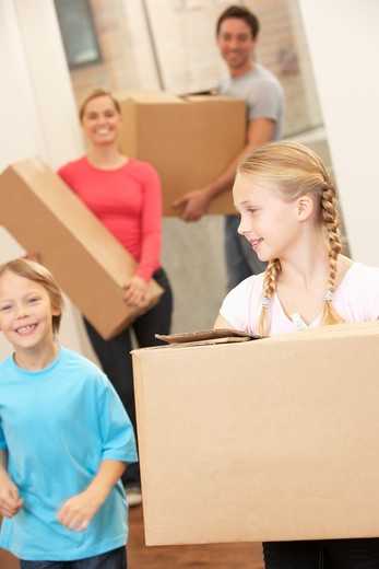 Family happy on moving day carrying cardboard boxes : Stock Photo