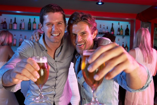Two Young Men Having Fun In Busy Bar : Stock Photo