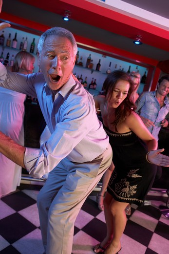 Stock Photo: 1888R-39739 Senior Man Dancing With Younger Woman In Busy Bar