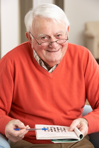 Senior Man Relaxing In Chair At Home Completing Crossword : Stock Photo