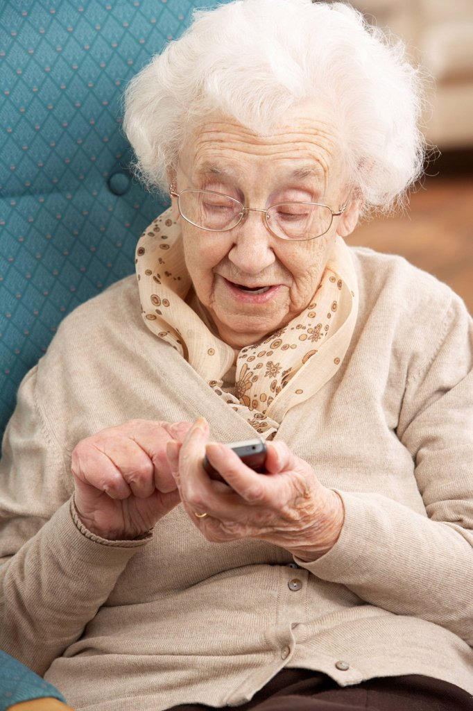 Stock Photo: 1888R-39995 Senior Woman Dialling Number On Mobile Phone Sitting In Chair At Home