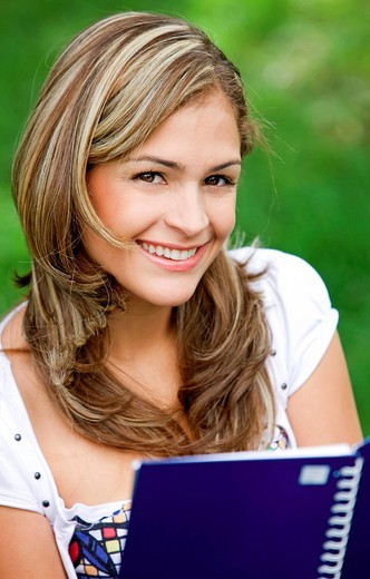 Stock Photo: 1888R-40527 casual female student smiling and holding a notebook _ outdoors