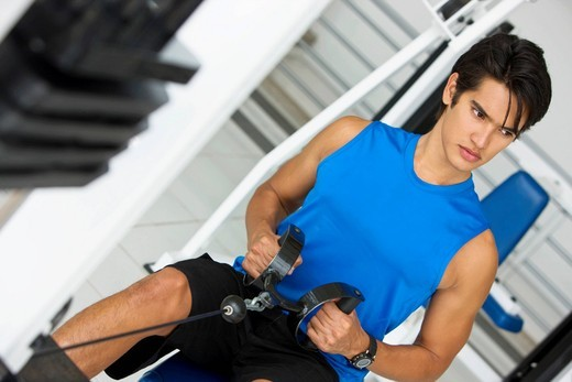 Stock Photo: 1888R-40582 Man exercising with the machines at the gym
