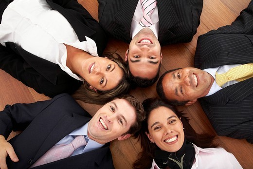 Stock Photo: 1888R-40887 business office team work _ group of young and successful businessmen and businesswomen on the floor with their heads together