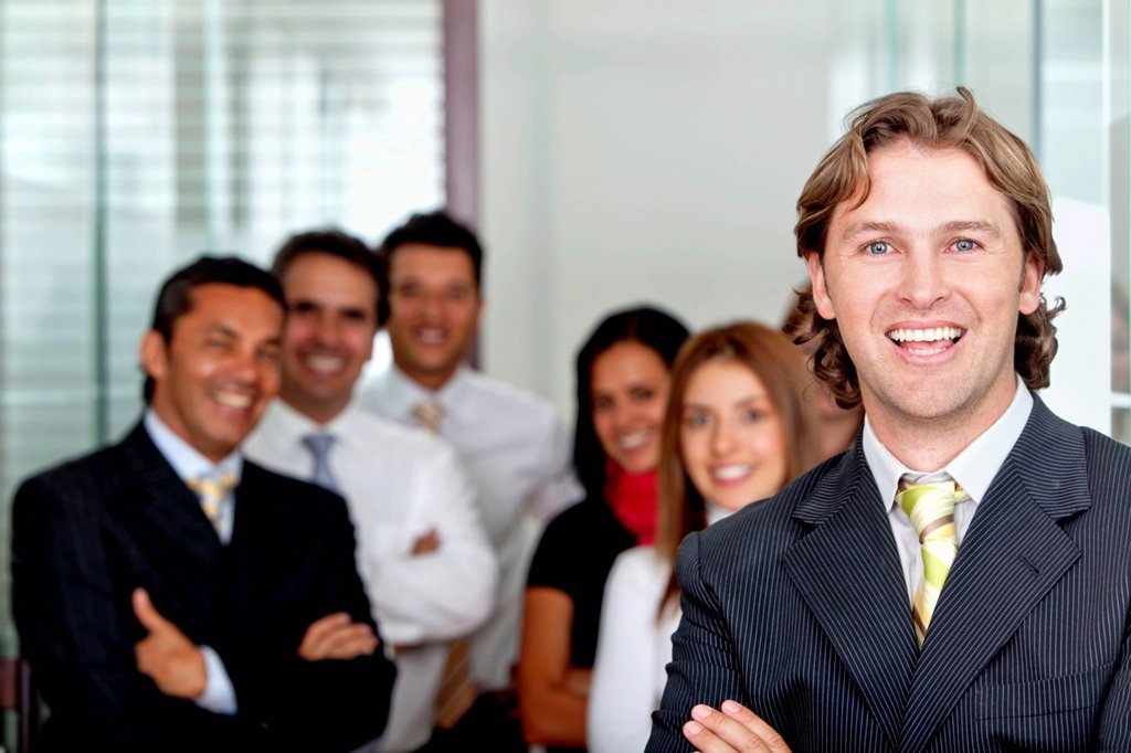 Stock Photo: 1888R-40961 Business man smiling at the office with a group behind