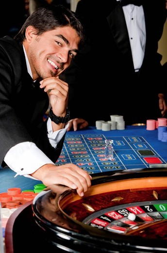 Man in a casino playing on the roulette. : Stock Photo