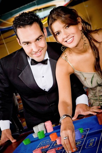 Couple at a casino playing on the roulette and smiling : Stock Photo