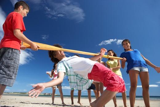 Teenagers doing limbo dance on beach : Stock Photo