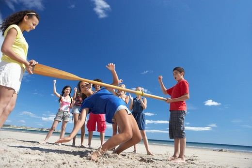 Teenagers doing limbo dance on beach : Stock Photo