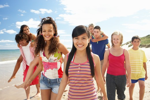 Teenagers walking on beach : Stock Photo