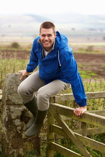 Man jumping over country gate : Stock Photo