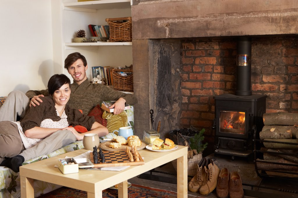 Stock Photo: 1888R-41502 Young couple relaxing by fire