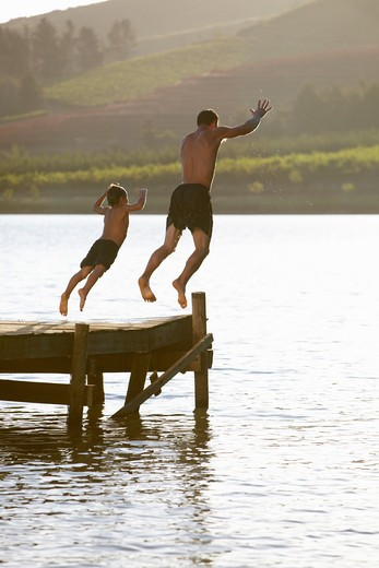 Young man with child jumping to water : Stock Photo