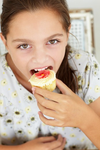 Stock Photo: 1888R-42090 Young girl eating cupcake