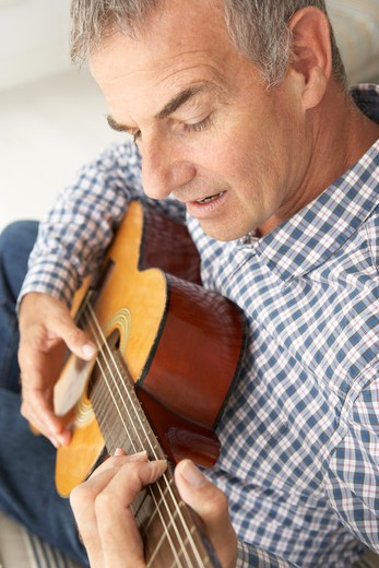 Mid age man playing acoustic guitar : Stock Photo