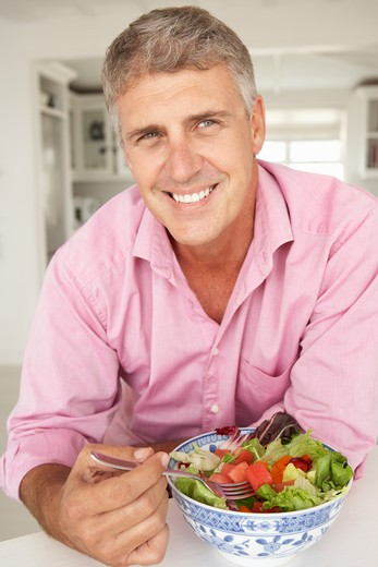 Mid age man eating salad : Stock Photo