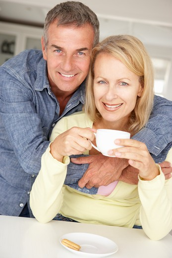 Stock Photo: 1888R-42308 Mid age couple with coffee at home