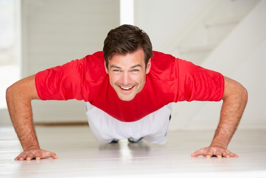 Man doing push-ups in home gym : Stock Photo