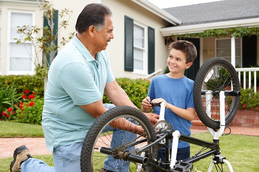 boy and grandfather fixing bike : Stock Photo