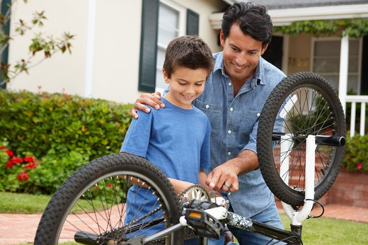 Stock Photo: 1888R-43193 Father and son fixing bike
